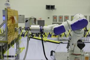 Робот, заправляющий макет спутника (phys.org)